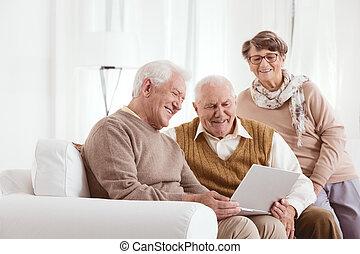 Elderly man showing laptop