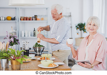 Senior woman and man in the kitchen - Senior woman with a...