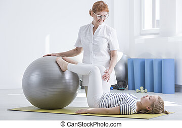 Child orthopedist using gym ball during rehabilitation with...