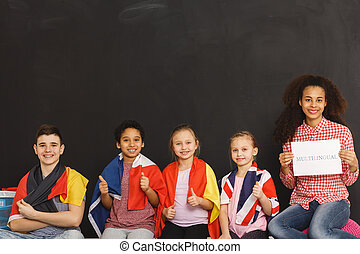 Kids with flags - Young kids different flags sitting next to...