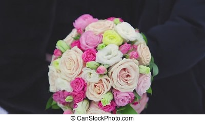 The bride and groom holding a bouquet and embracing, a wedding bouquet and hands closeup