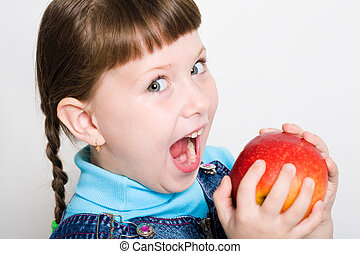 Eating apple - Cute girl looking aside with widely open...
