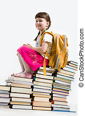 Sitting on books - Photo of smiling girl sitting on top of...