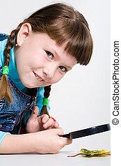 Cutie - Image of schoolgirl with magnifier in hand looking...