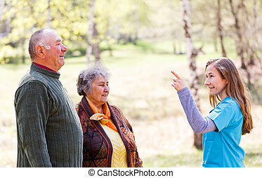 Elderly couple and young caregiver