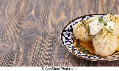 manti ravioli large dumplings on a plate with sour cream and...