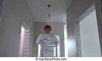 electrician man with helmet climb up on ladder and unscrew light bulb
