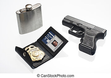 FBI Badge, flask, and gun on a table.
