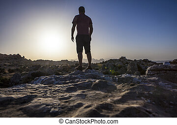 Man staring at sunrise over rocky ground. Torcal Natural...