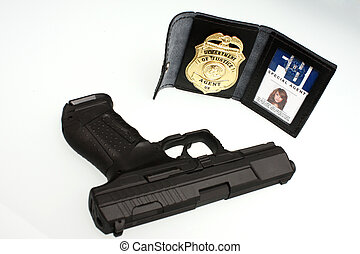 An FBI badge and pistol on a table