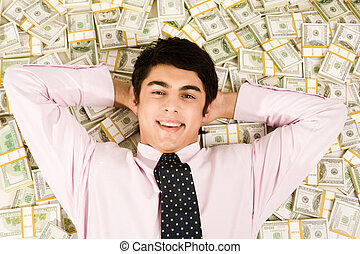 Prosperity - Image of happy businessman lying on heap of...