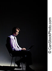 Working late - Photo of businessman working in dark room