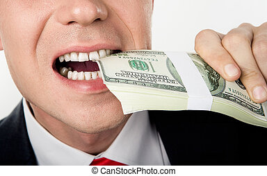 Biting money - Close-up of males mouth biting bill of...