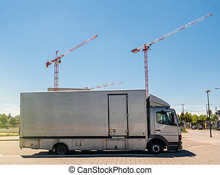 Silver truck parked on the street with construciton cranes working in the background