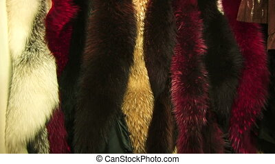 Natural fur - Elegant coats of fur weigh on the counter in...