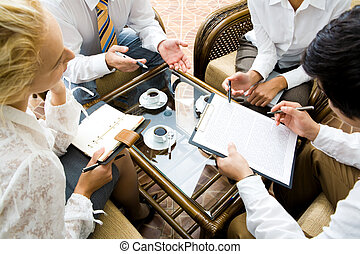 Discussion - Close-up of businesspeople discussing a plan at...