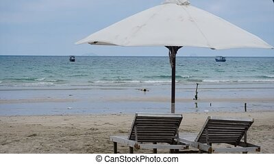 Tropical island sea shore and two deckchairs under parasol time lapse.