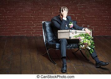 saddened by the groom sits in a chair with a suitcase and...