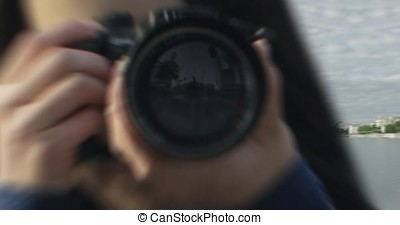 Photographer covering her face with the camera. Young women takes pictures with DSLR camera