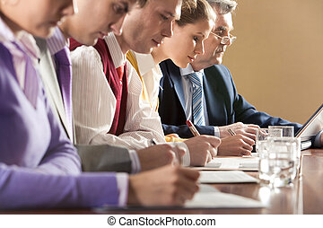 Briefing - Row of businesspeople writing review of their...