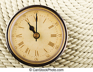 Clock with Roman numerals on cord background. 11