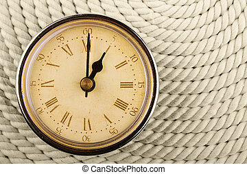 Clock with Roman numerals on cord background. 1