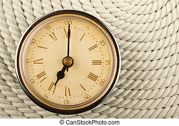 Clock with Roman numerals on cord background. 7