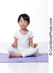 Asian Chinese little girl practicing yoga pose on a mat...