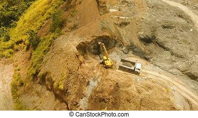 Excavator loads truck in quarry. Philippines,Bohol. -...