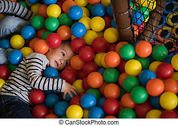 boy having fun in hundreds of colorful plastic balls - Young...