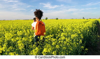 Girl teenager female young woman with red backpack and camera taking photograph in field of rape seed yellow flowers