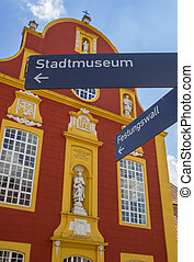 Tourist sign in front of the Gymnasial church in Meppen,...
