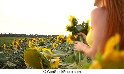 Young woman running across the field from sunflowers, slow motion