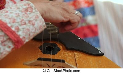 Folk music russian ensemble - woman plays the balalaika,...