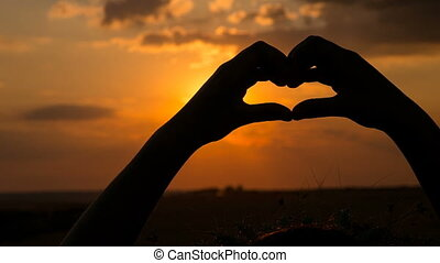 Silhouette of girl hands making heart symbol at sunset
