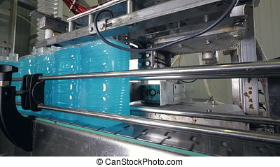 Large filled plastic containers on conveyor belt. - The...