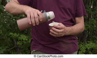 Man with a brown thermos outdoors. He is trying to pour tea,...