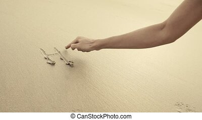 HELLO SUMMER written on the beach sand washed aways by waves.