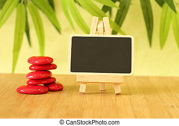 empty slate in width to write a message that is posed on an easel with  zen lifestyle red stones all on wooden floor and green foliage background