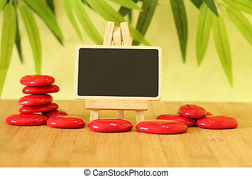 empty slate in width to write a message that is posed on an easel with red stones columns stones on floor and   in zen lifestyle all on wooden floor and green foliage background