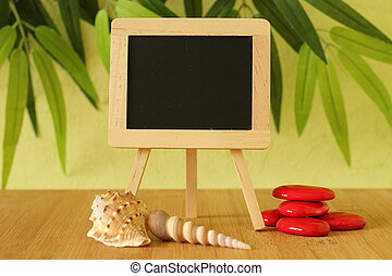 empty blackboard to write a message posed on an easel on a wooden floor with red pebble and beach shells on a green foliage background
