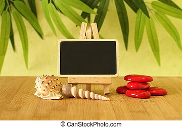 empty slate in width to write a message posed on an easel on a wooden floor with red pebble and beach shells on a green foliage background