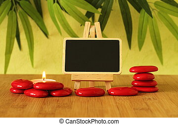 empty slate in width to write a message that is posed on an easel with red stones  columns on the ground in zen lifestyle with a candle all on wooden floor and green foliage background