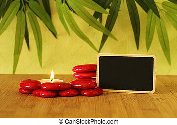 empty slate in width to write a message posed on the bamboo floor with red stones columns in the lifestyle Zen with a candle all on wooden floor and green foliage background