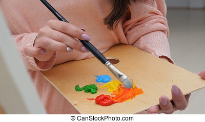 Female artist mixing colors close up. - Female artist...