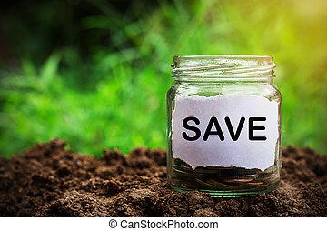 Savings money jar full of coins on soil
