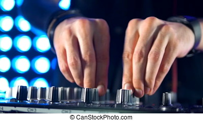 DJ equipment being used to play music. Hands close up.
