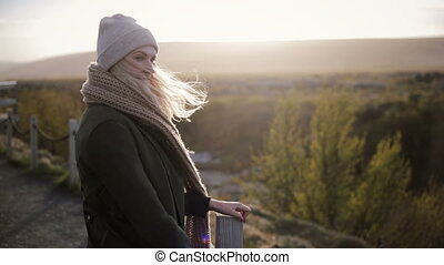 Young beautiful woman standing on the bridge in cold sunny...