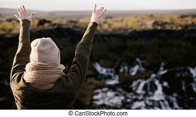 Happy woman standing near the Barnafoss waterfall in Iceland and jumping. Young female takes off hat and raises hand.