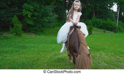 Little girl is riding a pony